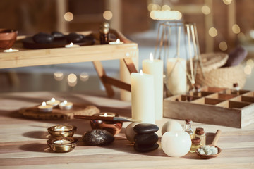 Glowing candles with spa supplies on table