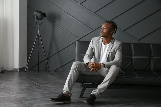 Portrait of stylish African-American man sitting on sofa in room