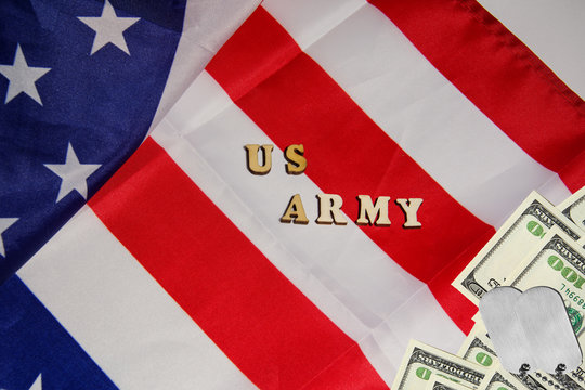 The soldier military tokens on dollar bills on the USA flag background with words US Army. Soldiers of fortune military power concept.