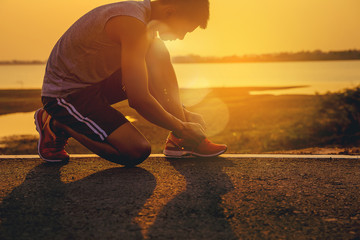 Stores à enrouleur Jogging Crop image of man runner lace his shoes and prepare to jogging with sunset background
