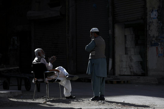 Shopkeepers talk outside their shops in the sunlight, to keep themselves warm during cold weather in Karachi