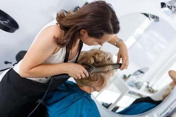 Stylist curling senior lady hair
