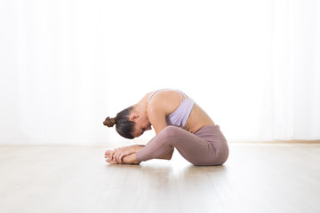 Fotomurales - Portrait of gorgeous active sporty young woman practicing yoga in studio. Beautiful girl practice Dandayamana Bibhaktapada Paschimotthanasana, standing separate leg stretching pose.