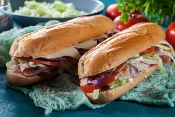 Submarine sandwiches with ham, cheese and vegetables