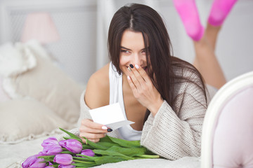 Young attractive woman with flowers reading a note from boyfriend. Lady indoors with flowers reading a message from lover. Valentine congrats.