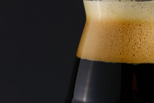 One tall glass of cold dark craft beer over black background. Close up. Copy space