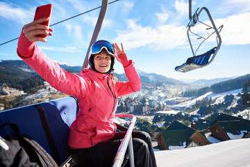 Young attractive woman, smiling skier in helmet, goggles and warm clothing riding in cable car high in air holding smartphone, taking selfie on winter ski resort background. Active lifestyle concept.