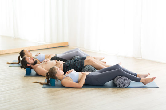 Restorative yoga with a bolster. Group of young sporty attractive people in yoga studio, lying on bolster cushion, stretching and relaxing during restorative yoga. Healthy active lifestyle.