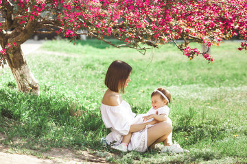 Closeup picture of young mother and her little daughter. Pretty family outdoor. Mom playing with her little cute child.