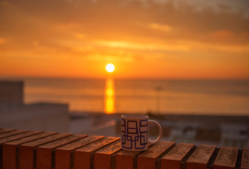 Tea cup with tea leaves in sunset
