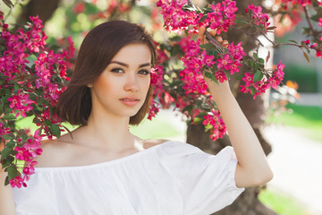 Beauty portrait. Young attractive woman with flowers. Closeup picture of beautiful lady outdoor on spring background. Pink petals.