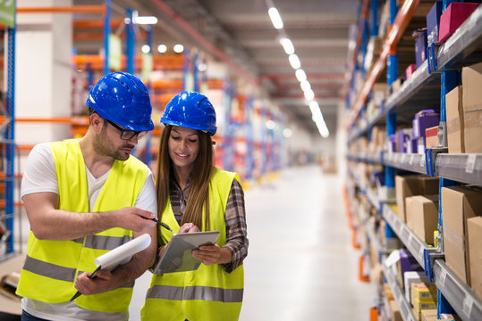 Warehouse workers checking inventory and consulting each other about organization and distribution of goods. Teamwork at warehouse storage department.