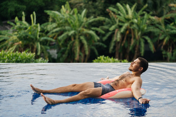 Attractive man enjoys a sun tan while lying in a swimming pool on a rubber ring. Luxury Holidays...