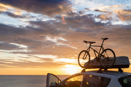 Mounted bicycle silhouette on the car roof with rising sun background. Dramatic sky at mediterranean sea dawn.