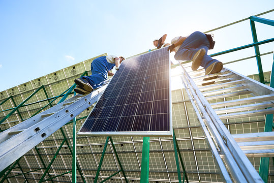 Solar battery screen installing by two mounters. Standing on ladders, mounting on metallic construction. Innovative electricity resources technologies. Ecological friendly, nature saving, economical.
