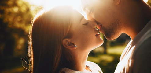 Close up portrait of a lovely young couple smiling before kissing against sunset with closed eyes outdoor in the park while dating.