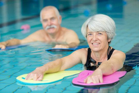 active senior doing aqua gym in outdoor swimming pool