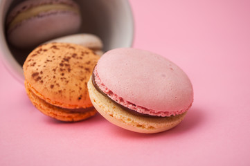 Foto auf Leinwand Macarons Closeup of french macarons and cup of coffee on pink background