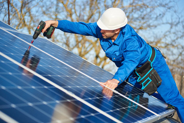 Man worker in blue suit and protective helmet installing solar photovoltaic panel system using screwdriver. Electrician mounting module on roof of modern house. Alternative energy ecological concept. Fotoväggar