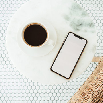 Blank screen mobile phone with empty copy space mockup on marble coffee table and mosaic tile. Flat lay, top view template for social media, website, blog, magazine.