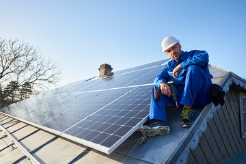 Male worker in blue suit and protective helmet installing stand-alone solar photovoltaic panel system using screwdriver. Professional electrician sitting on roof of modern house. Fotoväggar