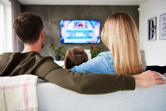 Rear view of family watching tv in living room