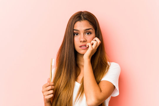 Young caucasian woman holding a toothbrush biting fingernails, nervous and very anxious.