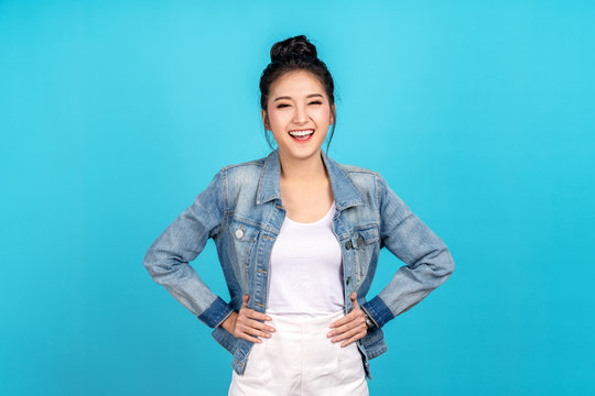 Portrait of Happy asian woman standing and feeling happiness and confident on blue background. Cute asia girl smiling or laughing wearing casual travel uniform in jeans shirt and keeping hands on hips