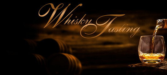 Whiskey tasting, whiskey is poured into a glass from a bottle, wooden barrels in the background Fototapete