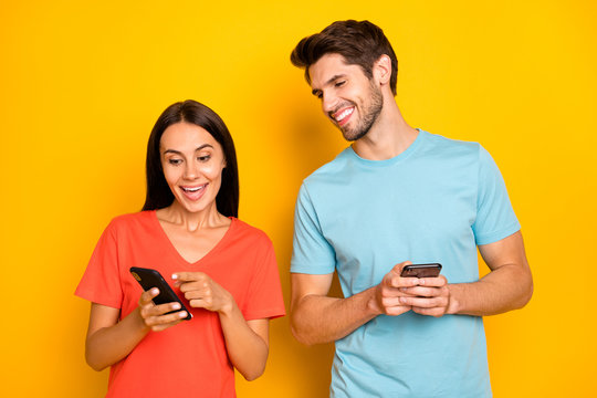 Photo of two funny guy lady people couple hold telephones showing finger positive comments reposts excited wear casual blue orange t-shirts isolated yellow color background