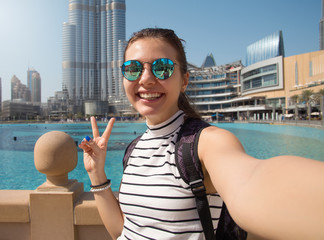 United Arab Emirates. traveler and photographer takes picture for her blog.Young happy tourist making selfie photo