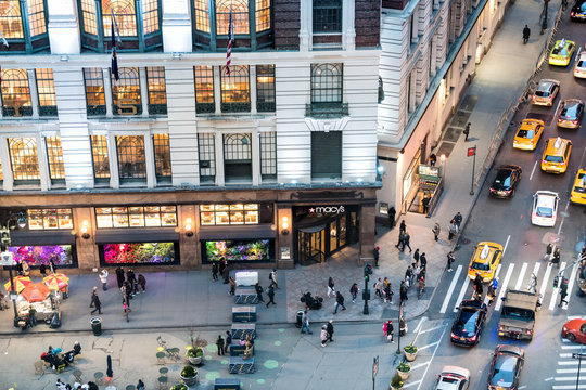 New York City, USA - April 6, 2018: High angle aerial view of Macy's store corner in NYC Herald Square midtown with crowd of people and traffic cars at night