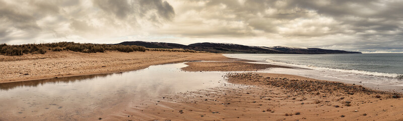 Dramatic winter clouds overshadowing Brora beach with snow on the hills