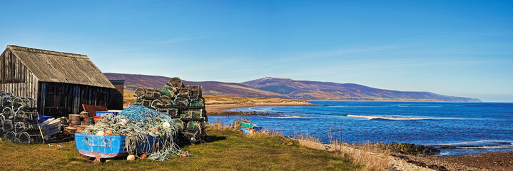 Old boat, stack of creels and shed at the mouth of the River Brora overlooking the Sutherland coastline and Brora beach