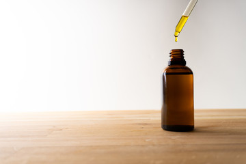 CBD oil or any other oil dropping into a small bottle standing on a wooden board - white background