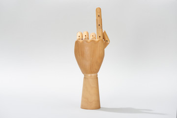 Wooden hand of puppet pointing with finger on grey background