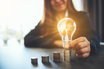 Businesswoman holding and putting lightbulb on coins stack on table for saving energy and money...