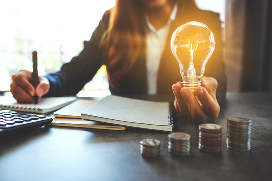 Businesswoman holding a lightbulb while taking note on notebook with coins stack on table, saving energy and money concept