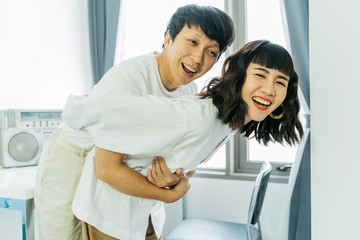 Happy young asian couple playing with happy together in room.