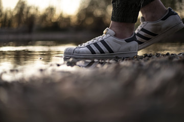 Young man wearing an old pair of Adidas Superstar shoes in a river water