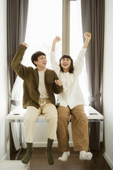 Young asian couple dancing together at home with happy.