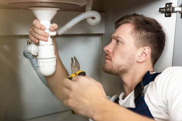 young handsome man plumber in uniform fixing the sink with pliers in his hand sitting on the kitchen floor professional plumbing repair service