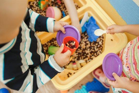Children play educational games with a sensory bin in kindergarten