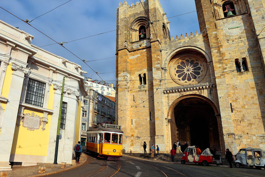 The iconic 28 tram in front of the Cathedral of St. Mary Major, simply called the Sé, into historic Alfama district, Lisbon, Portugal