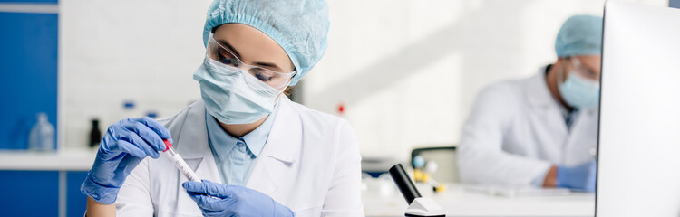 panoramic shot of molecular nutritionist holding test tube in lab
