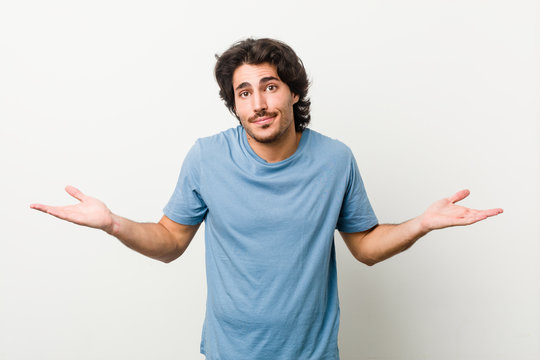 Young handsome man against a white background doubting and shrugging shoulders in questioning gesture.