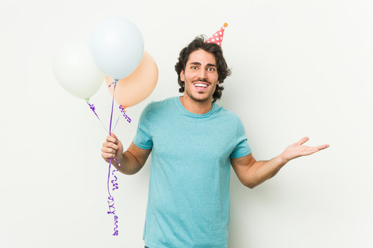 Young caucasian man holding balloons celebrating a brithday isolated in a grey background