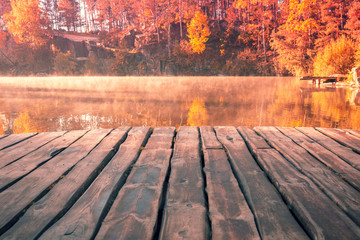 Poster Orange Glow Magical sunrise over the lake. Wooden deck on the lakeshore. Serene lake in the early foggy morning. Nature landscape