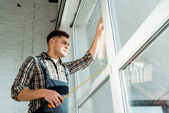 low angle view of installer standing near windows and holding measuring tape