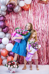 Happy and beautiful kids two girls with flowers on holiday together in pink photo zone